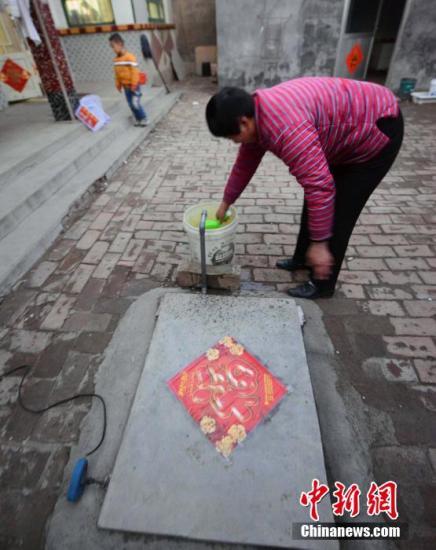 资料图:村民在自家院中贴有福字的水井旁用抽水泵取水。<a target='_blank' href='http://www.chinanews.com/'>中新社</a>发 刘可耕 摄