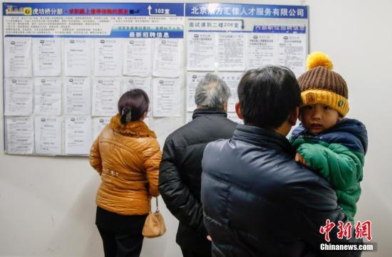 2月11日,北京市虎坊桥人才市场内,一名抱着孩子的应聘者正在观看招聘信息,大厅内求职者的数量与招聘人员的数量不相上下。春节过后,这里的招聘求职信息主要集中在餐饮行业。一名招工者说,求职者中一些人不具备相关的专业技能,但是对于比较低端的工作也不愿从事,就出现了招工难和求职难并存的现象。/p中新社发 张浩 摄