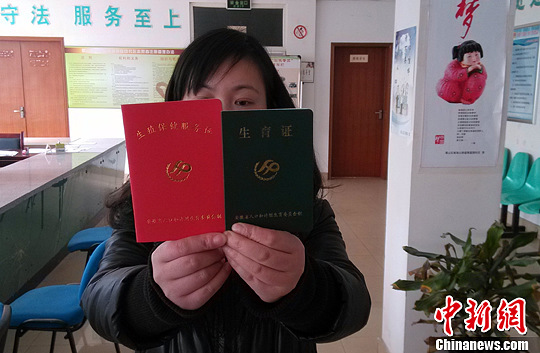 资料图:安徽省合肥市计生工作人员展示单独二孩生育证。中新社发 韩苏原 摄
