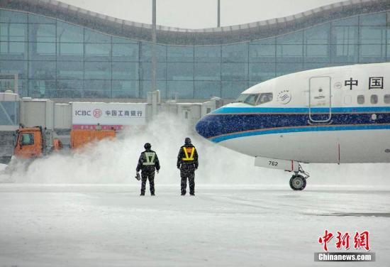 2月25日清晨,新疆乌鲁木齐国际机场,机务人员正清除积雪,保障延误航班能顺利起飞。2月24日9时许,乌鲁木齐飘起雪花,越下越大。截至2月24日23时,乌鲁木齐累计降雪量为12.3mm,达到暴雪级别。降雪造成乌鲁木齐国际机场八度关闭。图为机务人员雪中放行飞机。张思维 摄