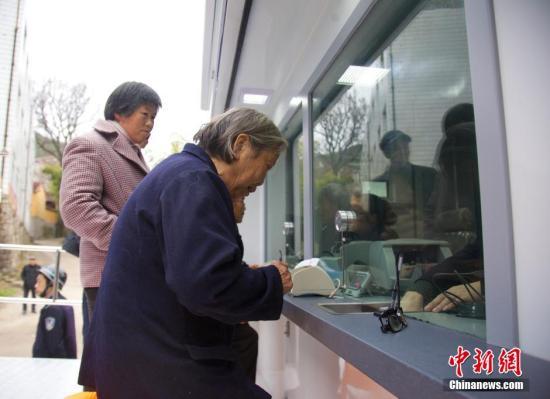 """2月28日,浙江台州临海仙人桥山区,老人在""""流动银行""""处办理金融业务。据悉,当地山区因无金融机构,百姓办理金融业务需到十公里外的镇区,极为不便。当地银行购置的流动服务车为他们带去便利。<a target='_blank' href='http://www.chinanews.com/'>中新社</a>发 林咸刚 摄"""