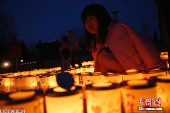 资料图:日本福?#28023;?#27665;众点燃蜡烛悼念2011年3.11地震海啸遇难者。