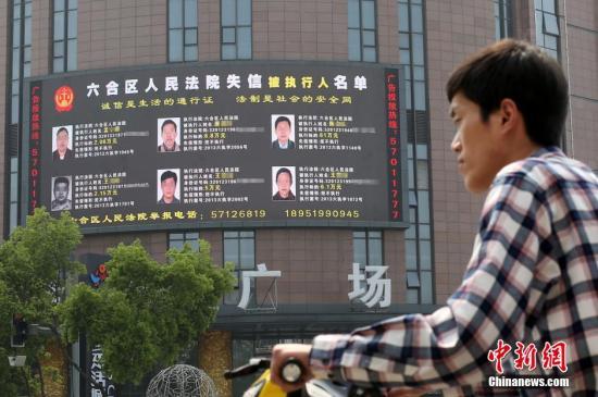 """资料图:南京街头的大屏幕滚动播放着""""老赖""""相关信息。a target='_blank' href='http://www.chinanews.com/'中新社/a发 泱波 摄"""