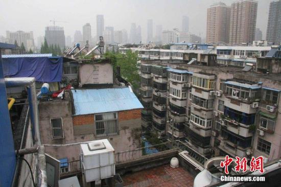 """4月17日,江苏省南京市,马府新村小区的""""空中棚户区"""",楼顶违建样式繁多。近日,有杭州曝出在市区的老旧小区屋顶,搭起""""空中棚户区"""",用来出租给外来务工人员。南京有没有这样的""""空中棚户区""""?记者也对南京的老旧小区进行了走访。昨天下午,记者来到了南京市玄武区进香河路小区,记者在小区的8栋楼层的屋顶,发现了近100间""""阳光房""""。而这里住的大多数是外来务工人员,其中一些是本地住户,另外还有一些住户在楼顶,搭建房子养鸽子,种青菜。雨田 摄 文字来源:南京晨报 图片来源:CFP视觉中国"""