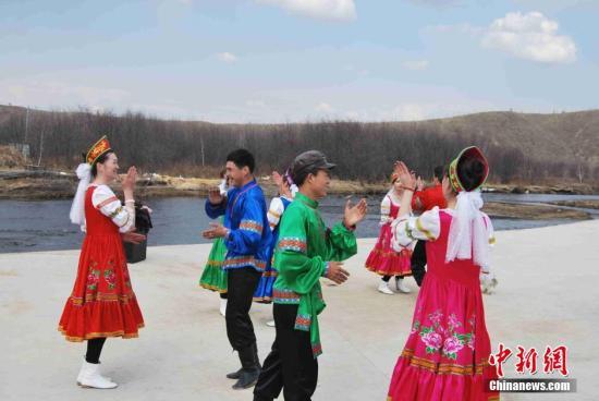 """20日-26日,内蒙古额尔古纳市俄罗斯族群众迎来了民族节日�D�D巴斯克节。巴斯克节是俄罗斯族一年中最隆重、最热闹的节日,勤劳的俄罗斯族群众提前打扫干净庭院,烤制出大量不同风味、不同造型的糕点,染制彩蛋,身着节日的盛装,跳起欢快奔放的俄罗斯族民间舞蹈。据资料记载,额尔古纳的俄罗斯族是19世纪未20世纪初,中国淘金和采伐男子与俄国女子""""始而相见以为友,继而相爱以为婚""""繁衍生息一代又一代华俄后裔,目前,已发展到第五、六代。张玮 摄"""