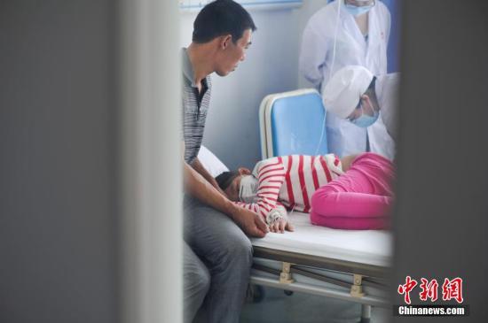 资料图:小金秋在做骨穿,父亲保其锋陪在身边,为她打气。刘冉阳 摄