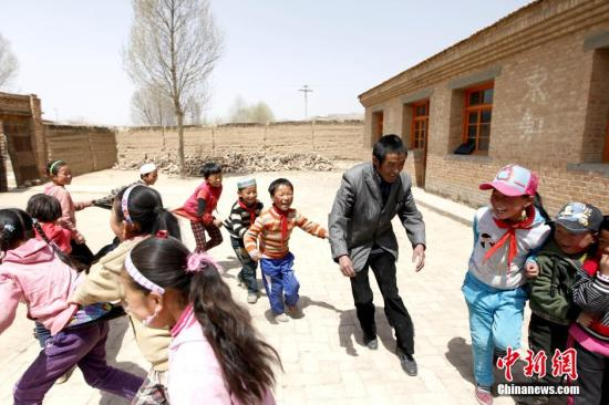 A teacher and his students in Qinghai. (File photo/China News Service)