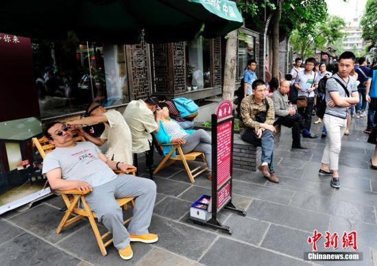 """""""五一""""小长假期间,在成都宽窄巷子特色街区吸引了众多民众前来观光游览。图为民众在成都宽窄巷子特色街区游览。安源 摄"""