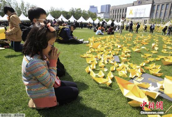 """资料图片:民众在首尔广场用黄色的纸张折成纸船,并摆放成爱心的模样,以追思、悼念""""世越号""""客轮沉没事件的遇难者。"""