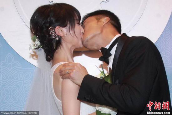 资料图:2014年5月11日,吴京谢楠婚礼举行, 两人互换戒指并亲吻。图片来源:CFP视觉中国