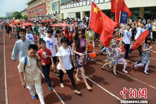 """资料图片:苏州新加坡国际学校""""国际家庭日""""启动。图为中国方阵进行列队展示。 王思哲 摄"""