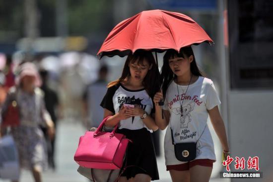 资料图:行人头顶骄阳出行。<a target='_blank' href='http://www.chinanews.com/' >中新网</a>记者 金硕 摄