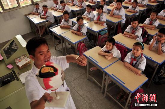 """6月4日,在6月6日全国爱眼日来临之际,江西省万载县第二小学开展""""保护眼睛从小做起""""活动,邀请当地人民医院眼科医生走进校园,通过讲解眼球构造、指导正确眼保健操等方式,向小学生普及眼保健知识,进行爱护眼睛、保护视力方面的健康知识教育。邓龙华 摄"""