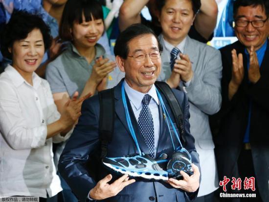 当地时间2014年6月5日,韩国首尔,现任首尔市市长、韩国最大在野党新政治民主联合候选人朴元淳在选举中获胜成功连任,击败对手执政党新世界党候选人郑梦准。朴元淳召开记者会庆祝胜利喜笑颜开,并获支撑者赠送的鞋子。