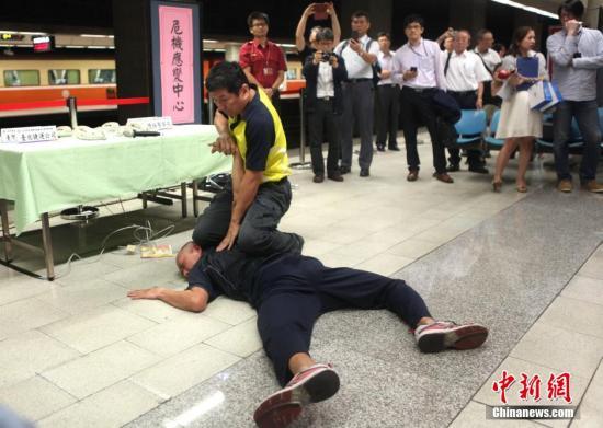 """6月12日,台湾铁路管理局等五个机构在台铁板桥站举行""""防暴应变演练"""",现场共有120多人参与。主办方表示,演练的目的,是希望""""三铁""""(台铁、高铁、捷运)加强AV视频 ,并与铁路警察和消防局、卫生单位进一步合作,确保发生突发事件时能最大程度保障乘客安全。图为警方演示擒拿术。发 陈小愿 摄"""