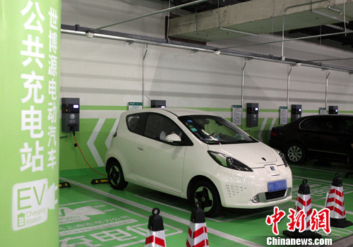 资料图:电动汽车在公共充电停车位充电。中新社发 张亨伟 摄