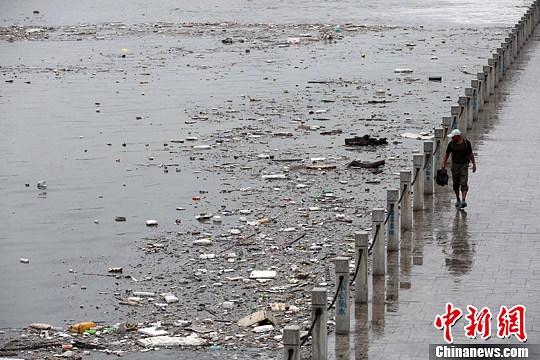 7月4日,山西太原遭遇暴雨袭击,雨水将大量垃圾冲入汾河公园河道内,致使河面漂浮大面积垃圾,造成河水污染。中新社发 武俊杰 摄