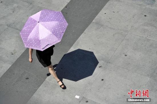 资料图:民众打伞防晒。 <a target='_blank' href='http://www.chinanews.com/' >中新网</a>记者 金硕 摄