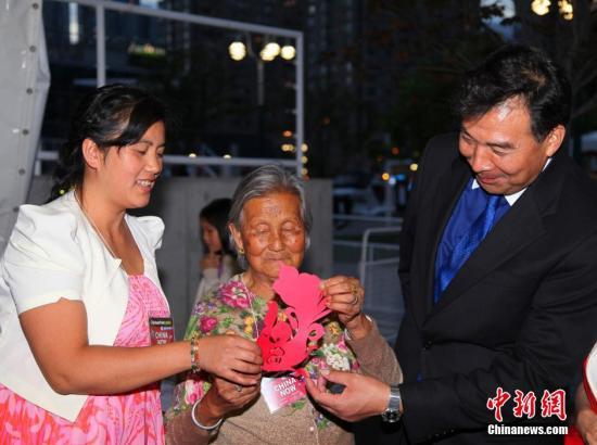 """当地时间7月11日晚,中国和加拿大文化交流史上迄今为止规模最大的一次中国民俗文化主题活动�D�D""""2014年加拿大�D中国民俗文化节CHINA NOW""""在多伦多安大略湖畔开幕。来自中国15个省的70多位表演艺术家和中国工艺的传承人,将古老的中国民俗文化搬到了这里,包括已有两千多年历史的杨柳青年画、泥人张泥塑、刺绣等。图为中国驻加拿大大使罗照辉(右一)慰问参加文化节的七十多岁的剪纸老艺人。中新社发 徐长安 摄"""