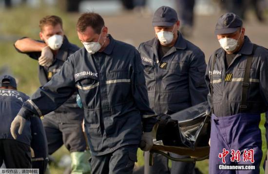 """當地時間2014年7月19日,烏克蘭Grabovo,救援人員在馬航M17墜機事故的現場。國際社會要求控制馬航MH17墜機事故現場的親俄武裝提供獨立調查擊落該機的兇手提供""""迅速、全面、可靠、暢通無阻的""""配合。"""