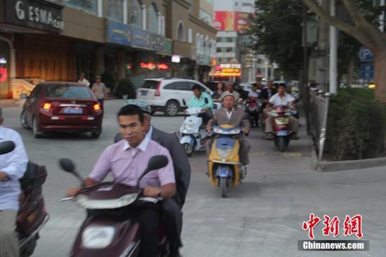 资料图:骑电动自行车出行的人们。朱景朝 摄