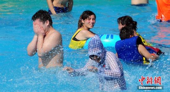 """资料图:武汉遭遇""""酷暑天"""",武汉玛雅水公园里游玩的市民穿着防晒衣在水中玩耍。中新社发 张畅 摄"""