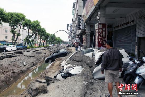 """2014年8月1日,台湾高雄市前镇区气爆废墟,场景惨烈,显见气爆威力巨大。图为路树、路灯和小轿车""""三叠""""倒地。当天临近子夜时分,当地发生重大的可燃气体外泄爆炸事故,破坏力惊人,造成人员大量人员伤亡。黄少华 摄"""