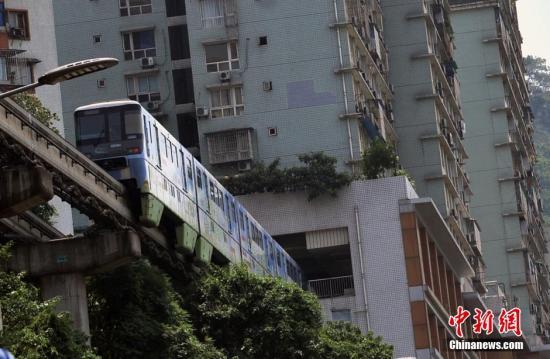 资料图:重庆轻轨2号线缓缓通过李子坝站台。 陈超 摄
