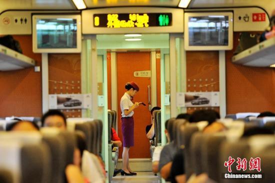 资料图:2014年8月8日,兰渝铁路高南线开通运营。图为D5176次动车乘务员为旅客服务瞬间。 安源 摄