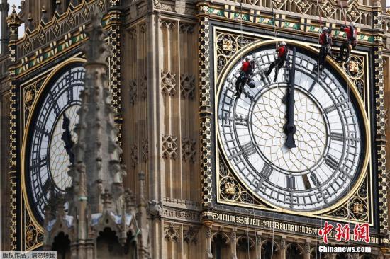 资料图:英国伦敦,工作人员吊在大本钟的钟面上进行清洁工作。