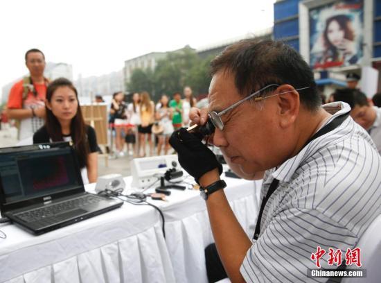 资料图:在北京崇文门街边举行的寺库奢侈品鉴宝会,吸引众多路人排队鉴宝。 <a target='_blank' href='http://www.chinanews.com/'>中新社</a>发 杜洋 摄