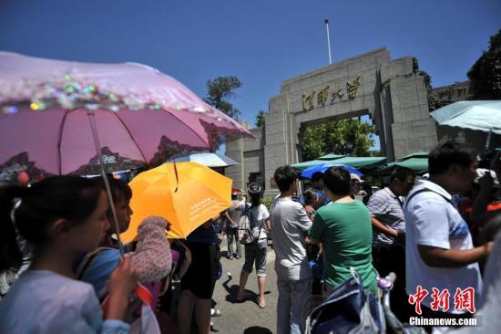 """近日,在刚刚结束的暑假期间,北京不少游客前往北大、清华等国内知名高校参观游览。在这几所高校周围,本来免费参观的校园却出了不少""""黑导游""""在周围叫价带人,使得原本安静学校环境和秩序遭到破坏。 图为等待进入清华大学校园参观的人群。<a target='_blank' href='http://www.chinanews.com/' >中新网</a>记者 金硕 摄"""