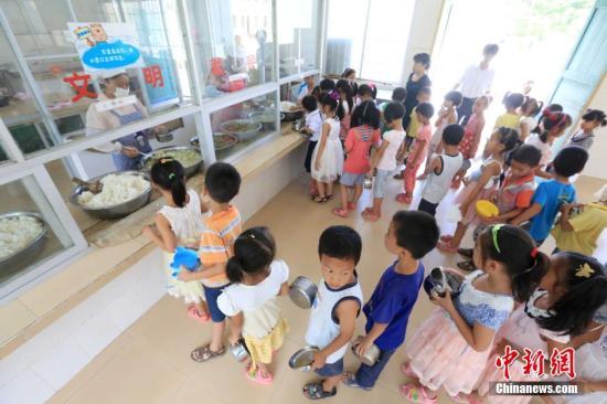 资料图:农村学生领取营养午餐。谭凯兴 摄
