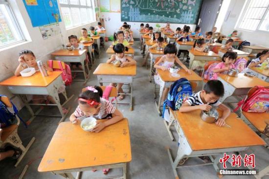 资料图:广西一小学学生在教室吃免费午餐。谭凯兴 摄