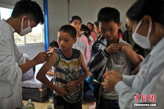 9月2日,云南魯甸震中新建的板房學校內,學生排隊接種甲肝和麻腮風疫苗,預防疾病。 中新社發 任東 攝