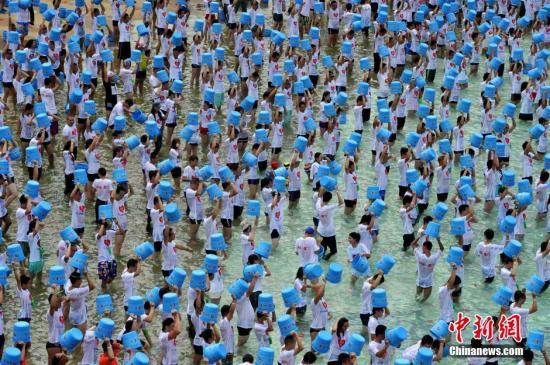 """9月6日,""""关爱渐冻人——千人冰桶挑战""""公益活动在厦门观音山水世界举行,来自海峡两岸的1000多位爱心人士一同浇下冰水,力争打破吉尼斯世界纪录,为渐冻人救助公益项目筹集善款。本次活动由海峡导报社主办,他们与中国医师协会""""融化渐冻人的心""""渐冻人救助公益项目达成合作,活动所募集的善款全部捐给这个项目,用以救助渐冻人。与之前国内一些""""冰桶挑战""""活动主要以明星和企业家参与不同,本次活动主要是通过报纸、微信、微博等渠道,按自愿原则广泛发动普通读者和市民,每人只需捐100元就能参与。活动受到了厦门台商协会、两岸企业和高校、医院等单位的积极响应。王东明 摄"""