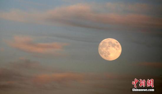 资料图:一轮圆月高挂天边,在晚霞的映衬下下十分俏丽。 发 卜向东 摄 图片来源:CNSPHOTO