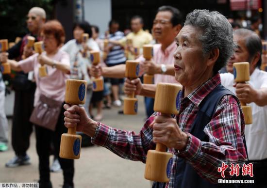 """资料图:日本老人们手持木质哑铃齐跳""""广场舞""""。"""