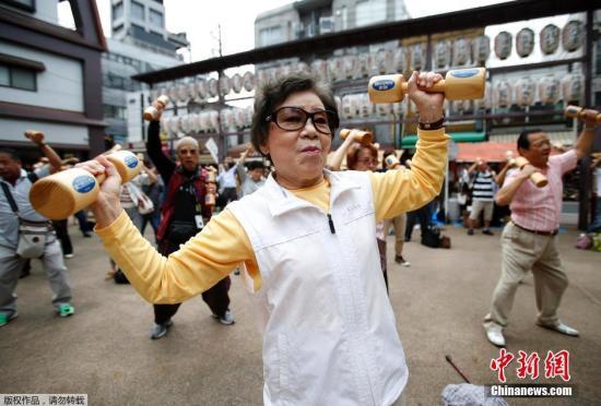 """资料图:日本老人们手持木质哑铃齐跳""""广场舞""""宣传健康活动。"""