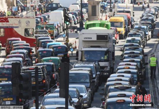 """资料图:当地时间2014年9月24日,英国伦敦,出租车""""排队""""阻塞怀特霍尔街进行示威,抵制Uber打车应用和拼车行为。"""