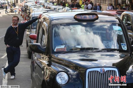 """资料图:出租车""""排队""""阻塞怀特霍尔街进行示威,抵制Uber打车应用和拼车行为。"""