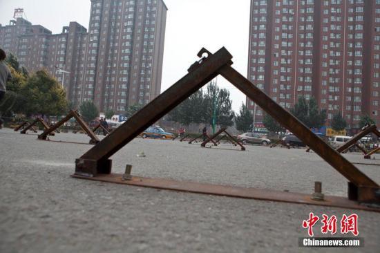 资料图:市民从一布满车位地锁的小区门前走过。<a target='_blank' href='http://www.chinanews.com/'>中新社</a>发 张瑶 摄