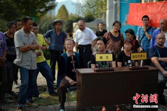 2014年10月9日,重庆,审判桌搬到人行道上、国徽挂在树杈间,一场家庭财产纠纷案在江北区石马河街道桂花园社区马路边开庭。图片来源:CFP视觉中国