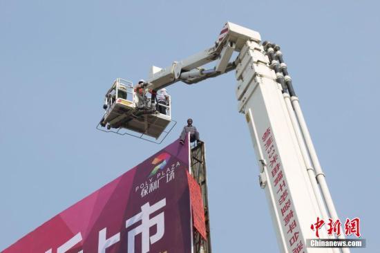 10月10日,一名脸部涂黑的男子爬上广西柳州市柳太路一块约20米高的户外广告牌,引来市民围观。经过消防官兵用云梯与该男子近距离沟通,4小时后该男子被成功救下。据警方调查,该男子有精神病史,在2013年曾有过一次类似行为。 王运鹏 摄