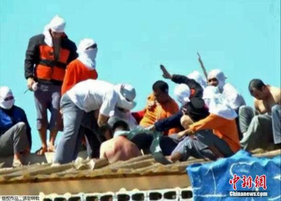 资料图:2014年10月14日,巴西巴拉那州,当地监狱爆发骚乱,蒙面囚犯将12名警卫和部分囚犯扒光作为人质挟持至屋顶。