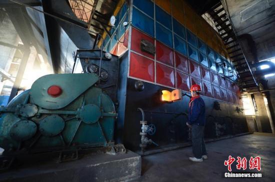 原料图。内蒙古呼和浩特一燃煤锅炉房内,做事人员操作供暖设备。中新社发 刘文华 摄