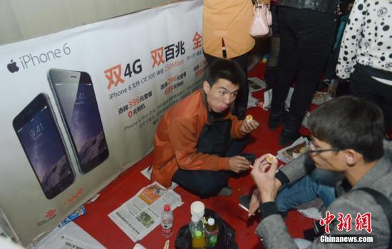 10月16日,山西太原联通营业厅门外,民众排队等待购买iPhone6。10月17日0点,备受关注的国行iPhone6和iPhone6 Plus裸机将在中国大陆销售。与此同时,中国联通、中国电信和中国移动三大运营商也启动预售,新一轮的市场大战拉开序幕。<a target='_blank' href='http://www.chinanews.com/'>中新社</a>发 韦亮 摄