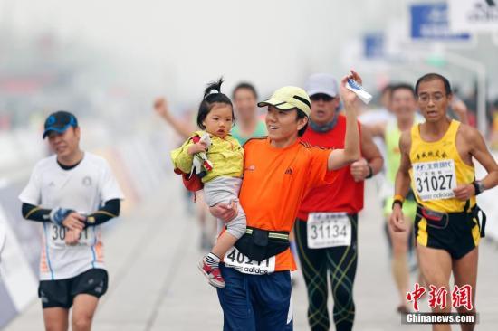 资料图:2014年北京马拉松.严重的雾霾难阻人们的健身热情.中新社图片