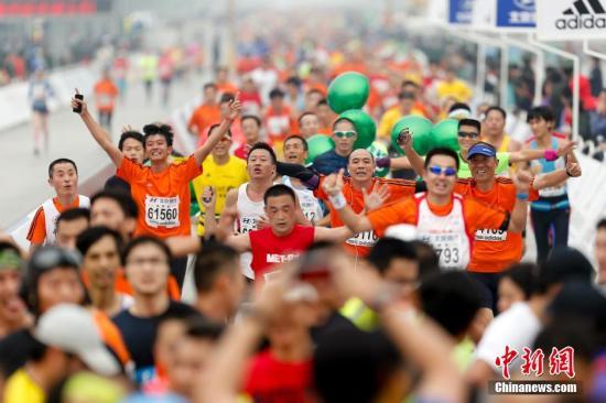资料图:往年北京马拉松赛。图为全程马拉松终点,参赛选手高举双手冲刺。中新社发 盛佳鹏 摄