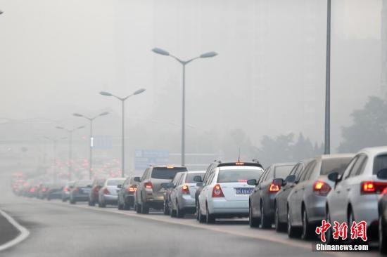 10月20日,北京,立交桥上的汽车在雾霾中缓慢前行。当日,北京仍然处在大雾、霾黄色预警和空气重污染蓝色预警中。 <a target='_blank' href='http://www.chinanews.com/'>中新社</a>发 盛佳鹏 摄